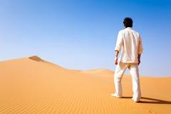 Hombre que se coloca en una duna de arena fotografía de archivo libre de regalías