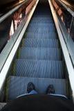 Hombre que se coloca en una escalera móvil Foto de archivo