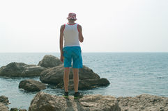 Hombre que se coloca en una roca Imagenes de archivo