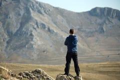 Hombre que se coloca encima de la montaña Imágenes de archivo libres de regalías