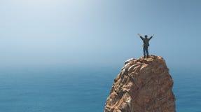 Hombre que se coloca encima de un acantilado de la roca Imágenes de archivo libres de regalías