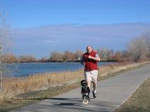 Hombre que se ejecuta con el perro al lado de un lago Fotos de archivo libres de regalías