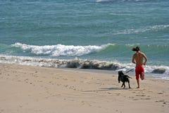 Hombre que se ejecuta con el perro en la playa Imagen de archivo libre de regalías