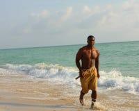 Hombre que se ejecuta en la playa Foto de archivo