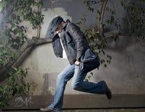 Hombre que se ejecuta lejos a lo largo de la pared Foto de archivo