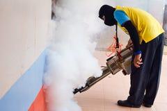 Hombre que se empaña para prevenir la extensión de la fiebre de dengue en Tailandia foto de archivo