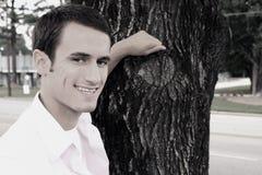 Hombre que se inclina en la sonrisa del árbol Imágenes de archivo libres de regalías