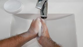 Hombre que se lava difícilmente las manos con mucho jabón en fregadero del cuarto de baño con agua desapasible metrajes