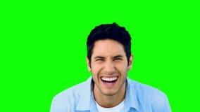 Hombre que se ríe de la cámara en la pantalla verde almacen de video
