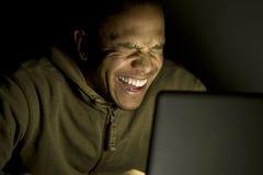 Hombre que se ríe de su ordenador portátil en la noche imagen de archivo libre de regalías
