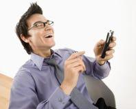 Hombre que se ríe del mensaje de texto. Fotografía de archivo libre de regalías