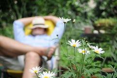Hombre que se reclina en el jardín Foto de archivo libre de regalías