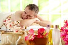 Hombre que se reclina en salón del balneario Foto de archivo libre de regalías