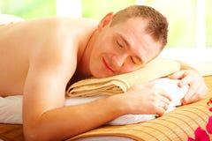 Hombre que se reclina en salón del balneario imagenes de archivo