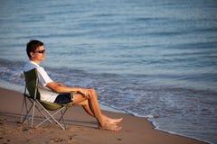 Hombre que se reclina sobre la playa Foto de archivo