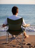 Hombre que se reclina sobre la playa Imágenes de archivo libres de regalías