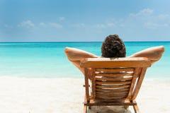 Hombre que se reclina sobre la playa Imagen de archivo