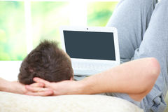 Hombre que se relaja con la computadora portátil Foto de archivo