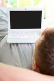 Hombre que se relaja con la computadora portátil Foto de archivo libre de regalías