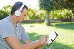 Hombre que se relaja con PC de la tableta Imagen de archivo