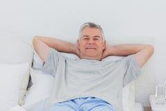 Hombre que se relaja en cama Imagen de archivo libre de regalías