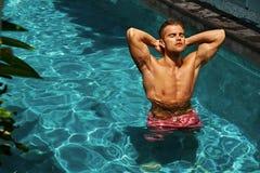 Hombre que se relaja en el agua de la piscina, Sun que broncea en verano placer Imagenes de archivo