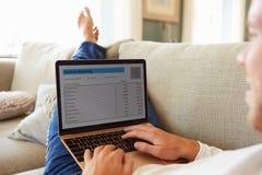 Hombre que se relaja en el ordenador portátil de Sofa Using Internet Banking On imágenes de archivo libres de regalías