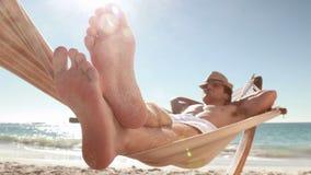 Hombre que se relaja en hamaca en la playa almacen de metraje de vídeo