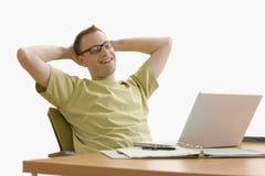 Hombre que se relaja en la computadora portátil - aislada Imagenes de archivo