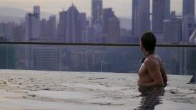 Hombre que se relaja en piscina del infinito imagen de archivo