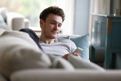 Hombre que se relaja en Sofa Checking Mobile Phone Imagenes de archivo