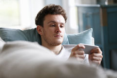 Hombre que se relaja en Sofa Checking Mobile Phone Foto de archivo