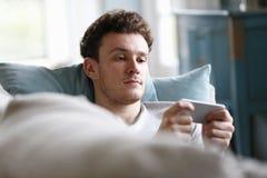 Hombre que se relaja en Sofa Checking Mobile Phone Fotos de archivo