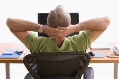 Hombre que se relaja en su escritorio Imagen de archivo
