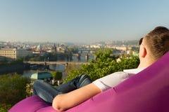 Hombre que se relaja en un sofá inflable Imágenes de archivo libres de regalías