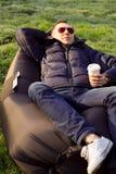 Hombre que se relaja en un sofá inflable Imagen de archivo