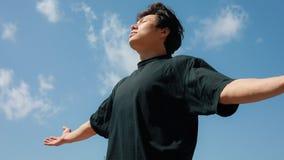 Hombre que se relaja en una libertad, fondo del cielo azul, manos aumentadas almacen de metraje de vídeo