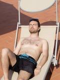 Hombre que se relaja en una piscina Foto de archivo libre de regalías