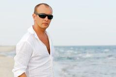 Hombre que se relaja por el mar imagen de archivo
