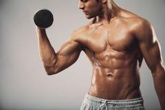 Hombre que se resuelve con pesas de gimnasia Fotos de archivo libres de regalías