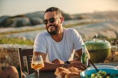 Hombre que se sienta al aire libre con las bebidas y los bocados foto de archivo libre de regalías
