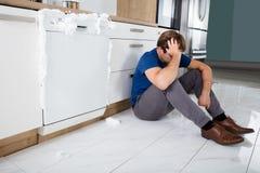 Hombre que se sienta al lado del lavaplatos Foto de archivo libre de regalías