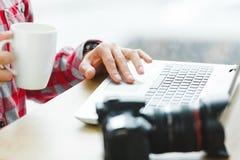 Hombre que se sienta con el ordenador portátil Imágenes de archivo libres de regalías