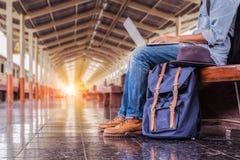 Hombre que se sienta con el ordenador portátil bolso del viaje en la estación de tren vendimia fotografía de archivo libre de regalías