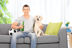 Hombre que se sienta con el perro en el sofá en casa Foto de archivo