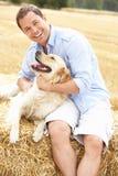 Hombre que se sienta con el perro en las balas de la paja en F cosechada Fotos de archivo