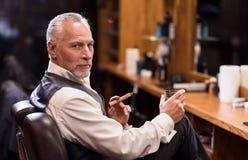 Hombre que se sienta con el vidrio y el cigarro del coñac imagen de archivo libre de regalías