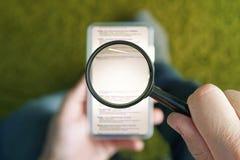 Hombre que se sienta con la lupa transparente sobre la página del Search Engine de la ojeada del smartphone Espacio de la copia p imagen de archivo