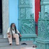 Hombre que se sienta delante del templo de Sri Veeramakaliamman imagenes de archivo