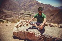 Hombre que se sienta en altas montañas Foto de archivo libre de regalías